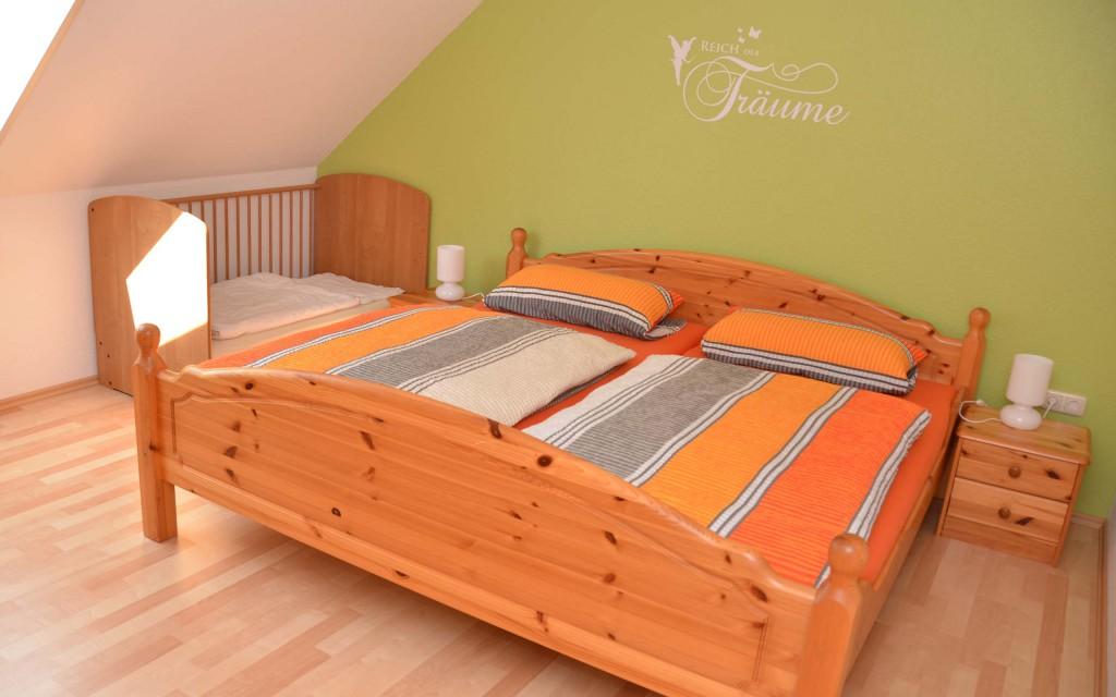 Schlafzimmer mit Kinderbett und Großem Doppelbett